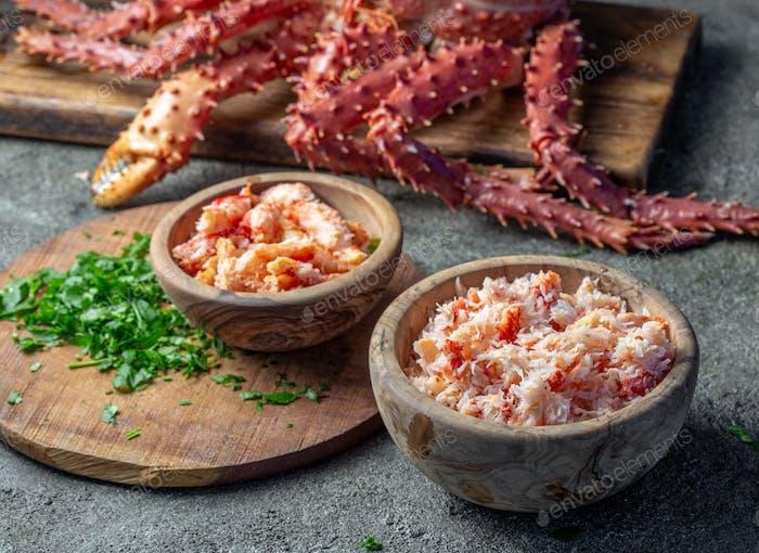 Krabbenfleisch von Königskrabben in Holzschale auf grauem Hintergrund.