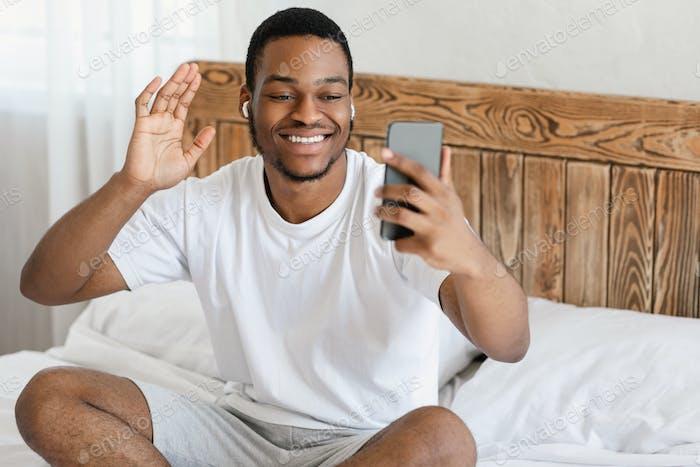 Fröhlicher afrikanischer Kerl macht Video anruf auf Handy im Schlafzimmer