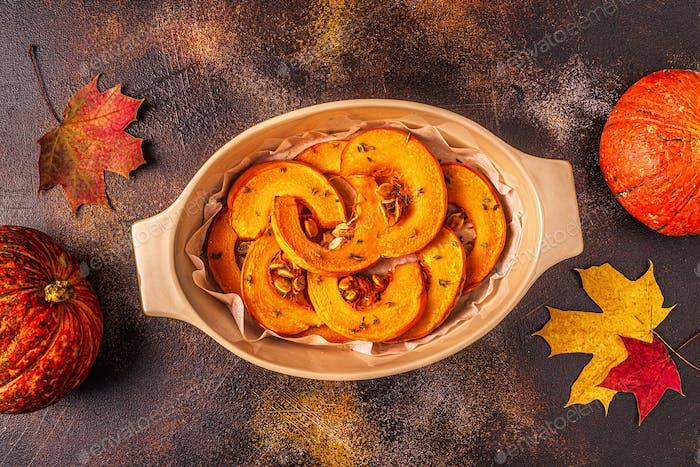 Baked slices of pumpkin on a dark background.