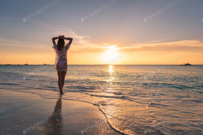 Beautiful young woman on the sandy beach at sunset