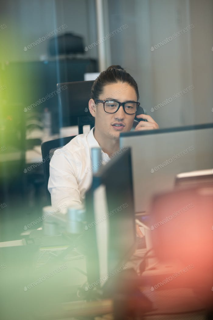 Businessman talking on phone while working in office