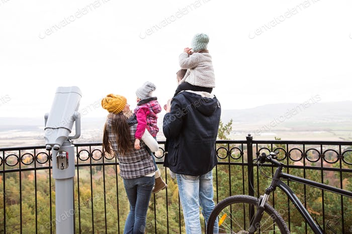 Young family in warm clothes with bicycle in autumn park