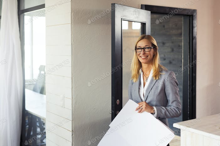 Woman holding blueprint in office