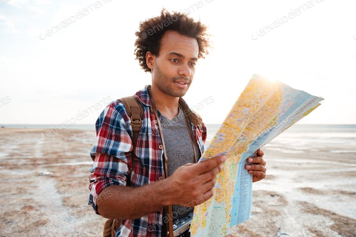 Handsome man in plaid shirt with map standing outdoors