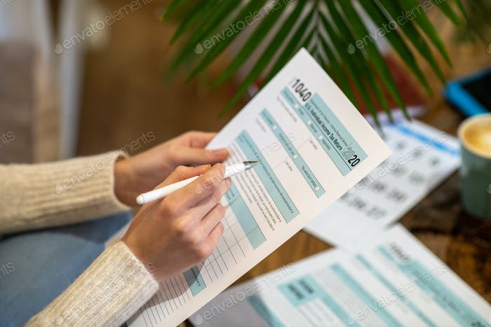 Woman holding the paper for counting tax expenses
