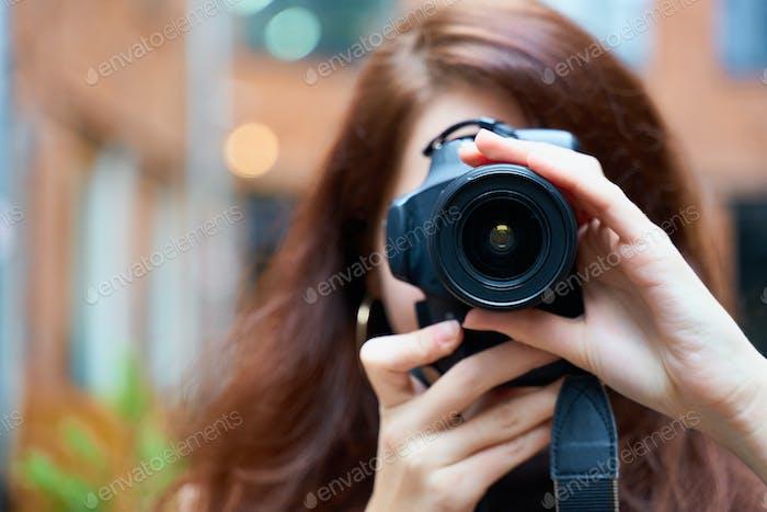 Schöne stilvolle modische Mädchen hält eine Kamera