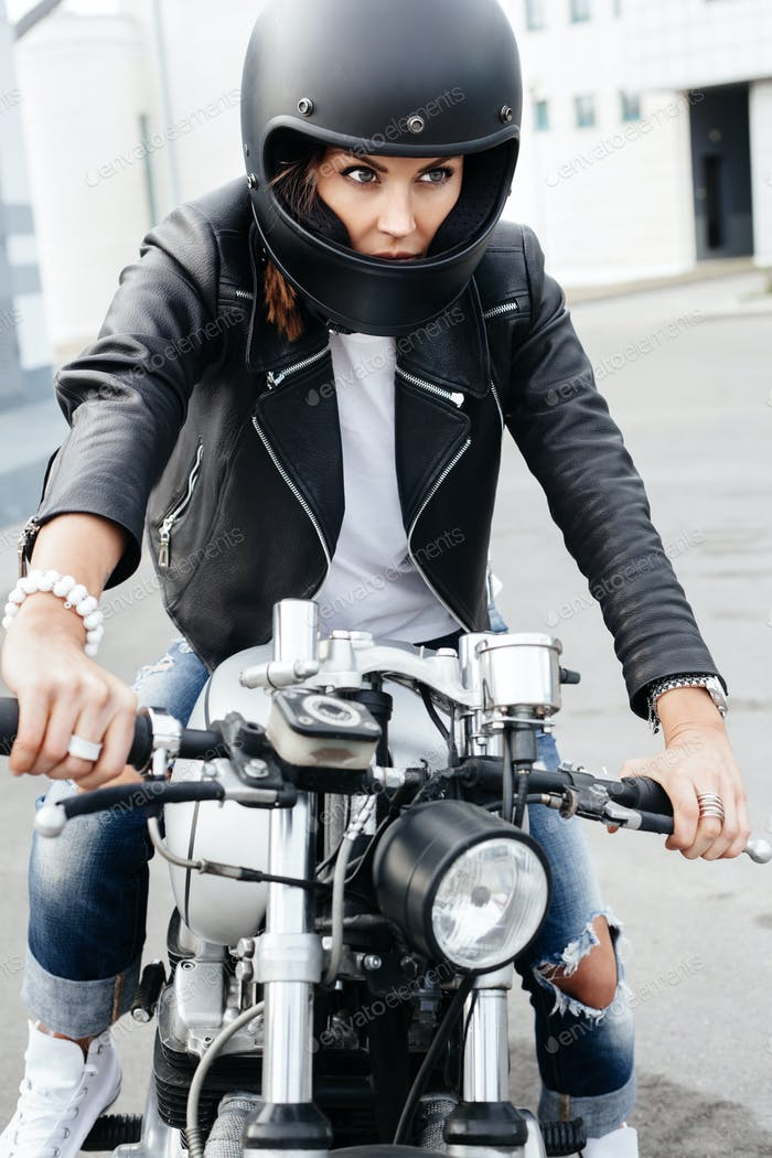 Biker girl in helmet on custom motorcycle