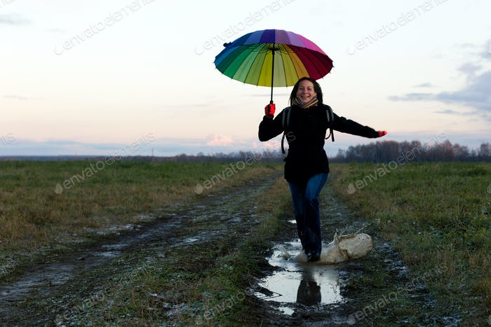 Young emotional woman with an umbrella on a walk, nature light