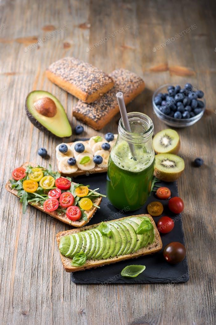 Gesunde Sandwiches mit Beeren, Avocado und Flasche Smoothie