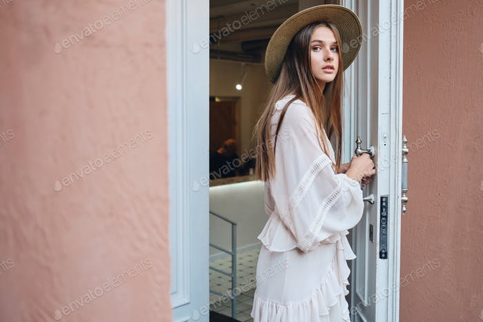 Beautiful girl in white dress and hat thoughtfully looking in camera opening white door of cafe