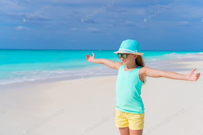 Cute little girl in hat walking at beach during caribbean vacation