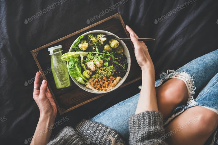 Healthy vegan bowl in bed, smoothie and woman in jeans