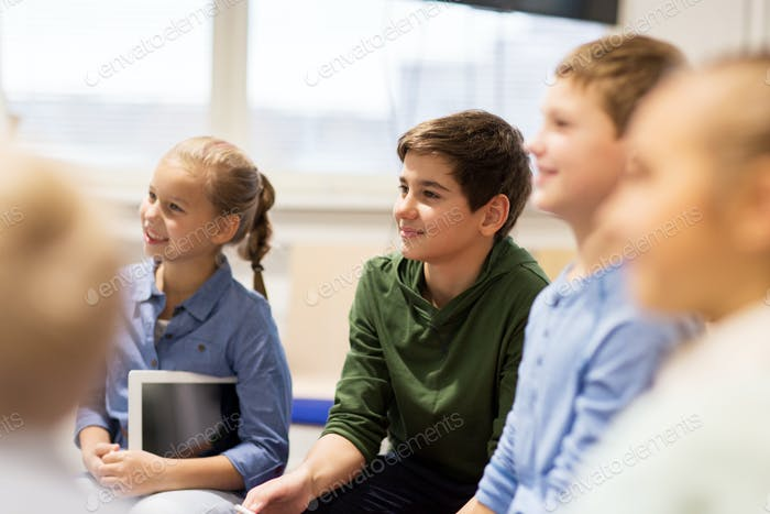 group of happy kids or friends learning at school