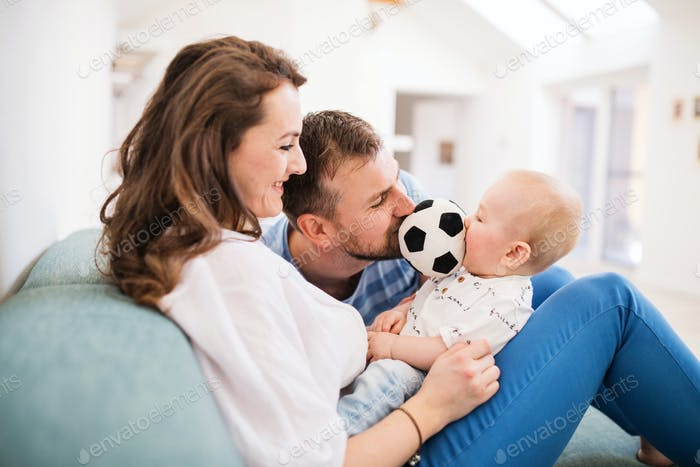 Young family with a baby boy at home, sitting on the sofa.
