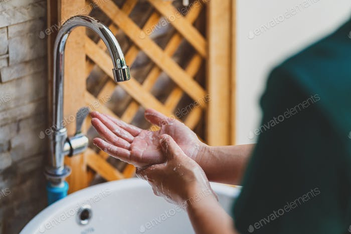 Rear view of hands washing with Chrome faucet and soap for Coronavirus pandemic prevention