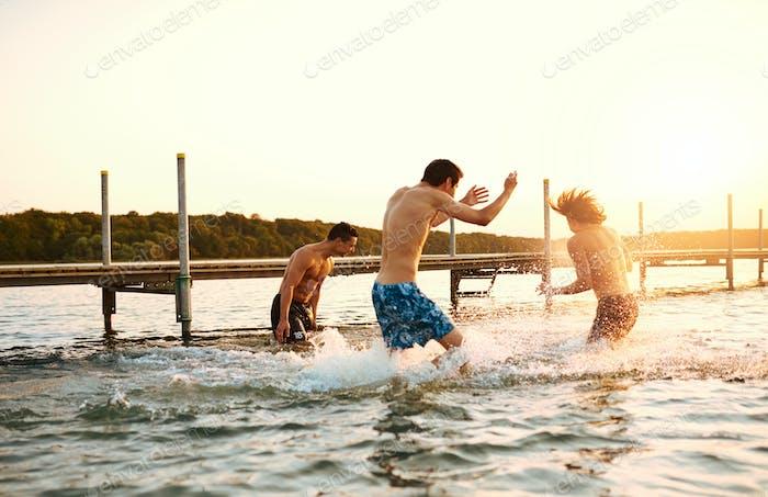 Three teenage boys playing in the water