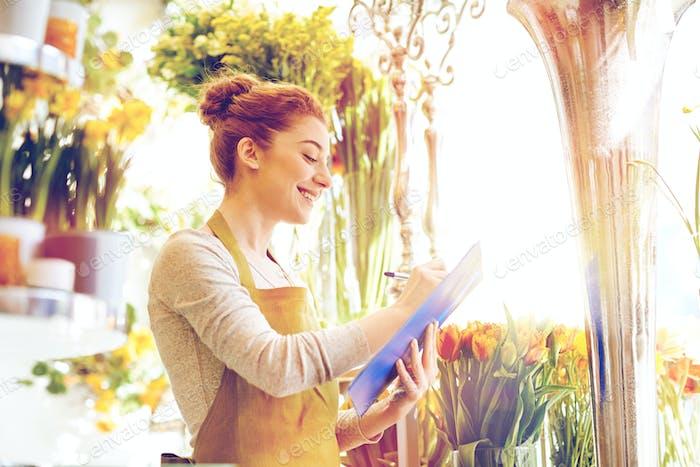 Blumenhändler Frau mit Klemmbrett im Blumenladen