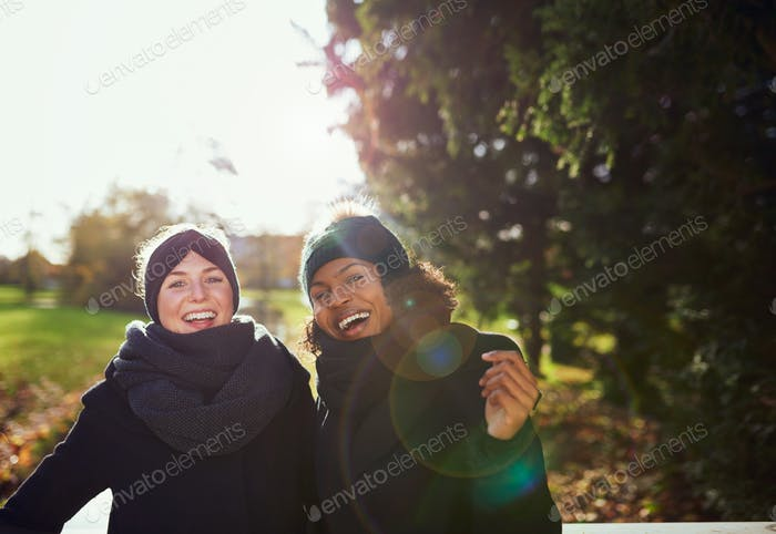 Two smiling women standing on bridge in park