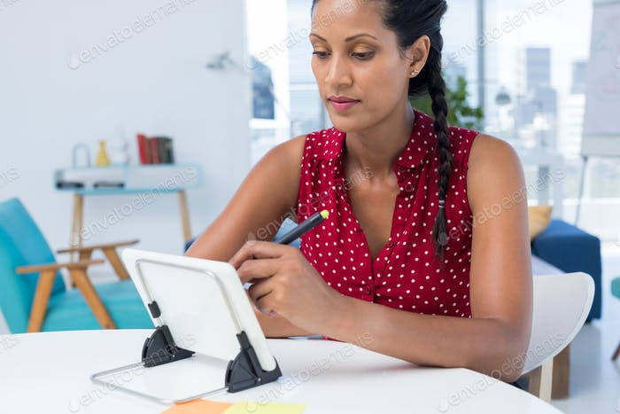 Female graphic designer using graphic tablet at desk