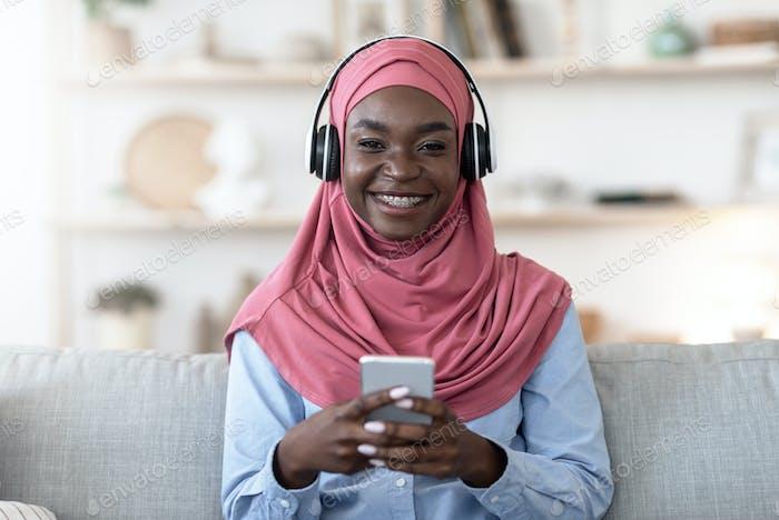 Favorite Leisure. Black muslim girl using smartphone and wireless headphones at home