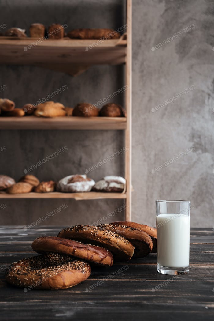 Pastries and glass of milk on dark wooden table