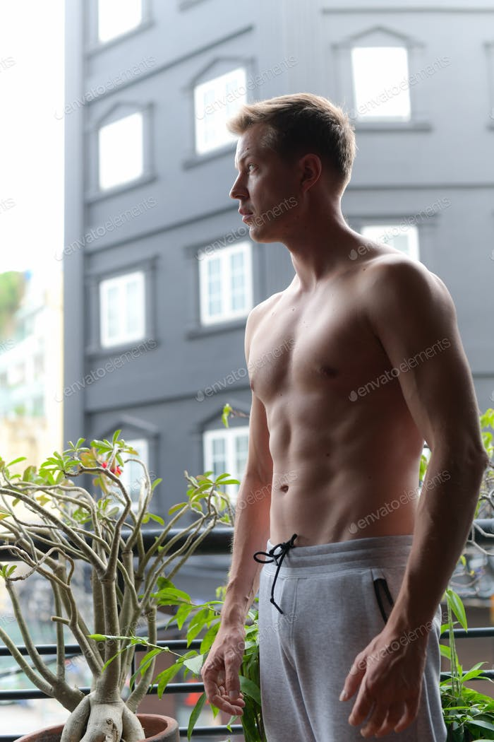 Handsome Shirtless Muscular Man Outdoors In Balcony Looking And Thinking