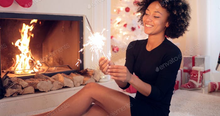 Fun young woman burning a sparkler for Christmas