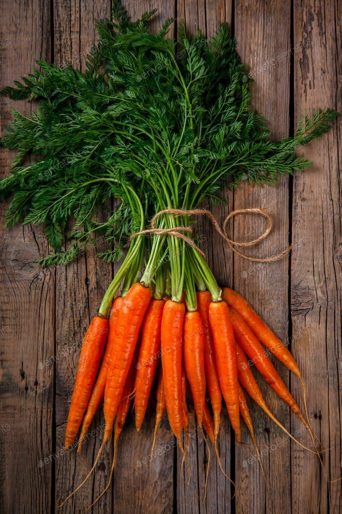 Bündel frische Karotten mit grünen Blättern