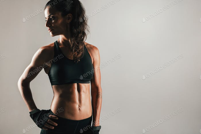 Muscular woman in shadow with abdominal muscles