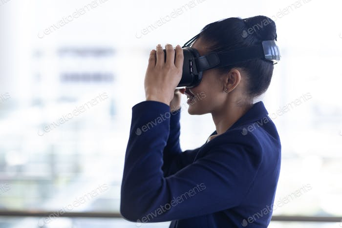 Side view of happy young mixed-race businesswoman using virtual reality headset in modern office