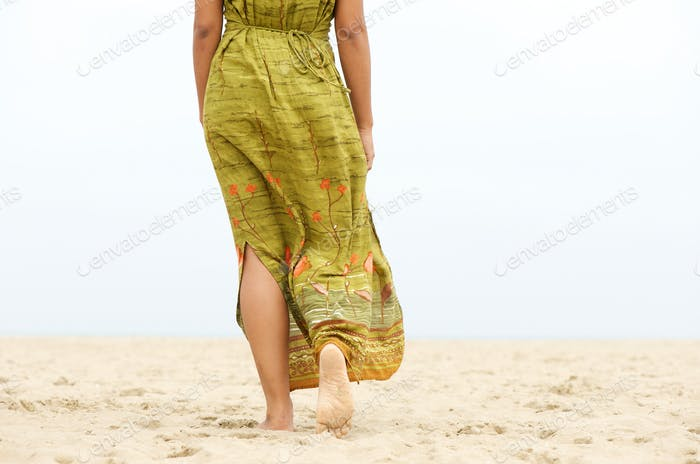 Portrait of a barefooted woman walking in the sand