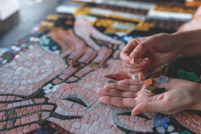 Female hands with mosaic