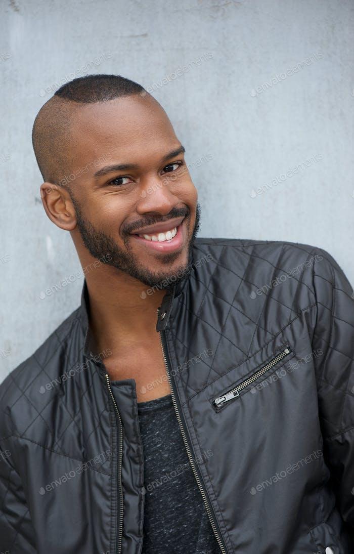 Vertical de un Alegre joven negro Hombre sonriendo al aire libre