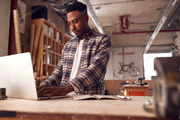 Male Craftsman In Carpentry Workshop For Bamboo Bicycles  Doing Accounts On Laptop