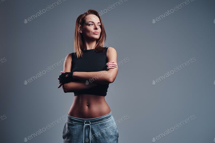Confident fitness woman wearing sportswear posing with her arms crossed.