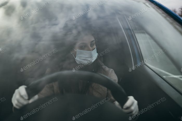 Young woman in a mask and gloves driving a car