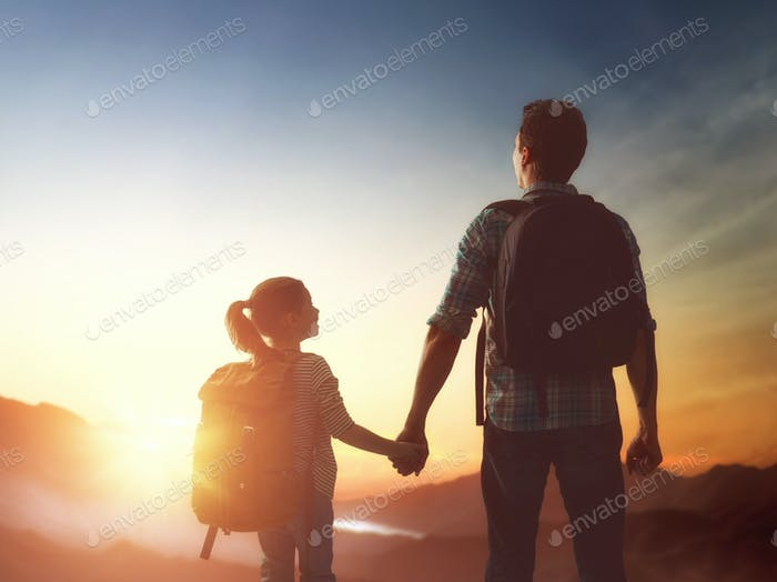 Kid and dad look at sunset