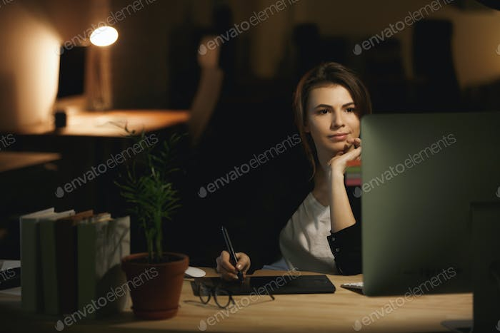 Serious young lady designer using computer and graphics tablet.
