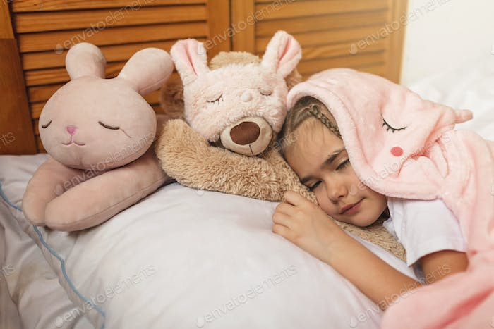 Top view of cute awaking girl with her toy animals wearing in light pink pajama with unicorn hoody