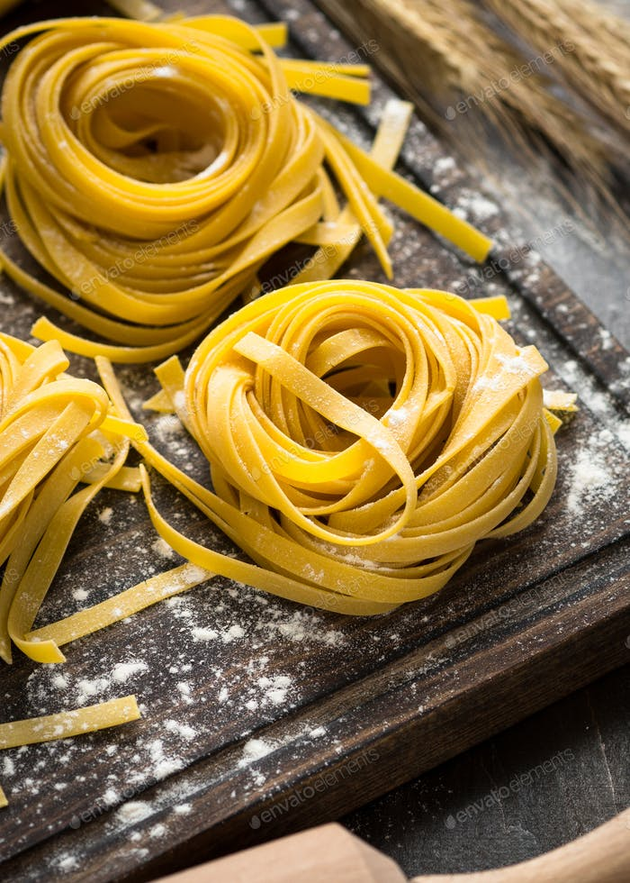 Fresh homemade pasta tagliatelle at wooden table.