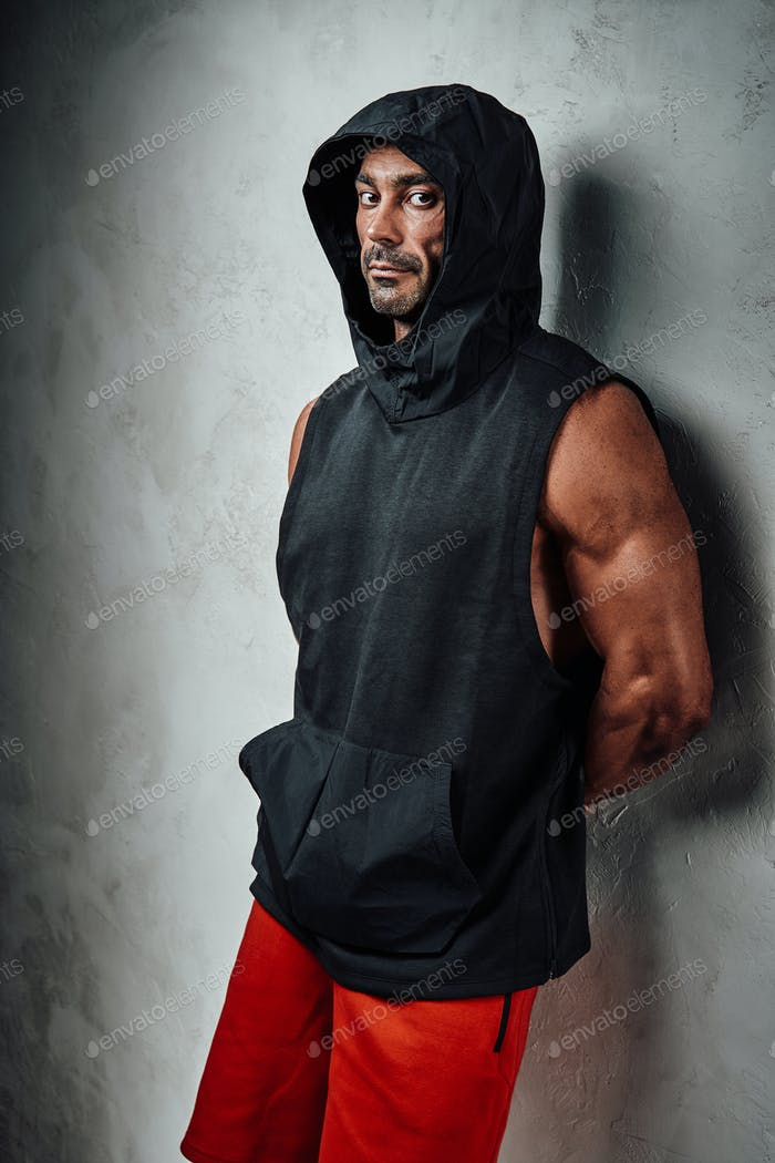 Handsome adult sportsman wearing sportswear posing in a dark studio while leaning on the wall