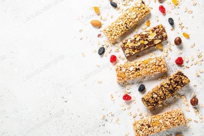 Granola bar with nuts, fruit and berries on white.