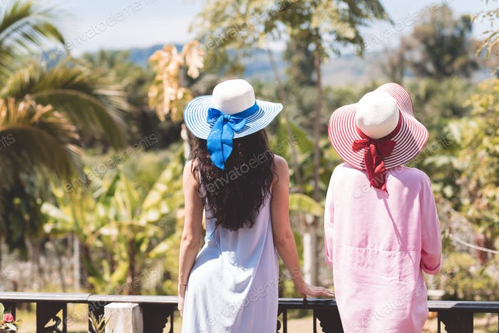 Back Rear View Of Young Women Couple Wearing Hats Over Beautiful Tropical Landscape