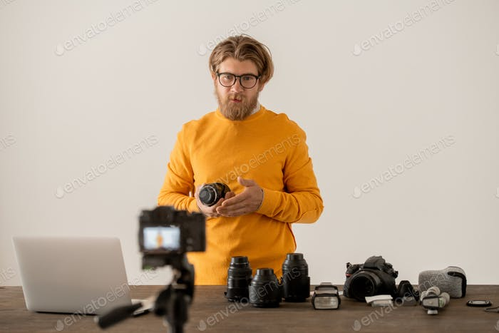 Bearded photographer showing component parts of new model of photocamera