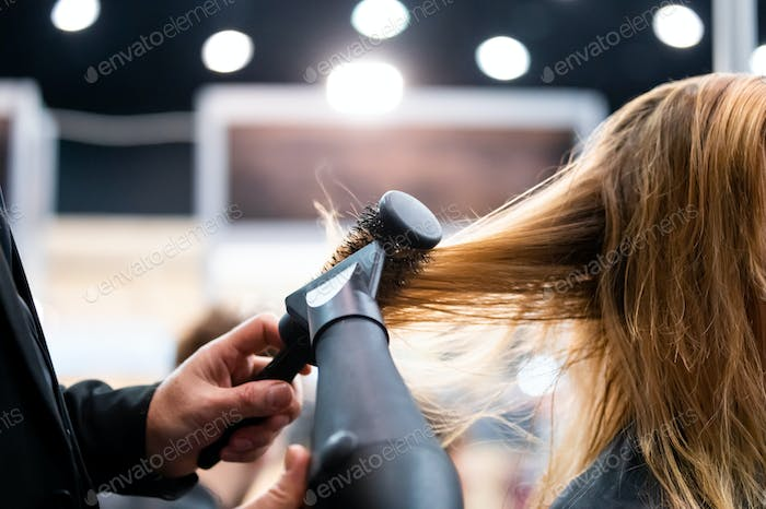 Drying hair with hair dryer and round brush close up