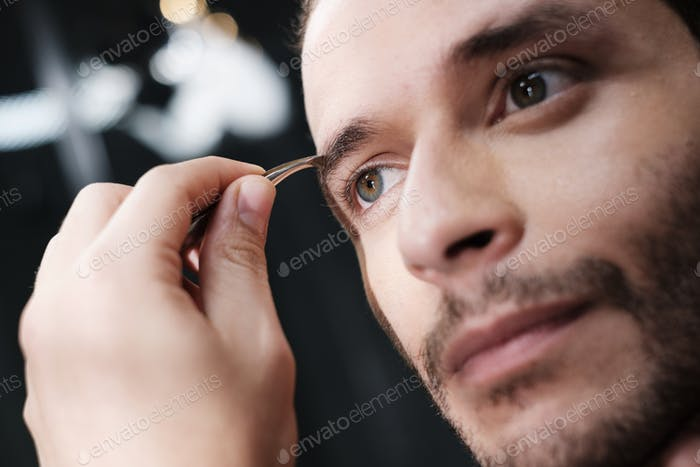Close Up Young Green Eyes Man Plucking His Eyebrows