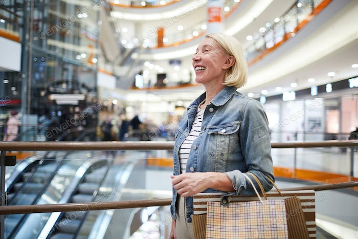 Positive mature woman going round shops in mall