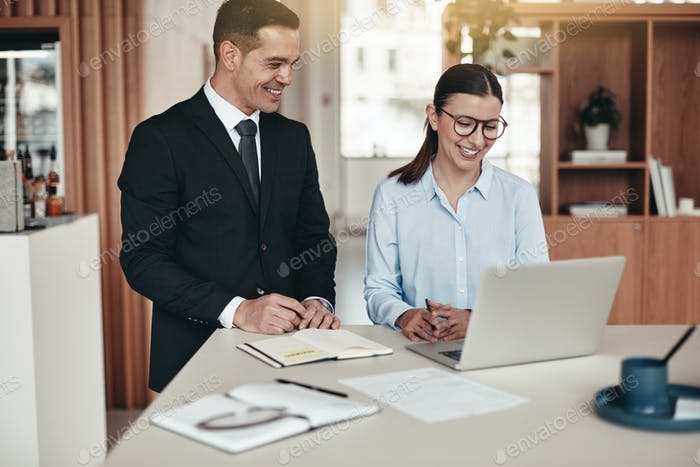 Two smiling businesspeople working together in an modern office