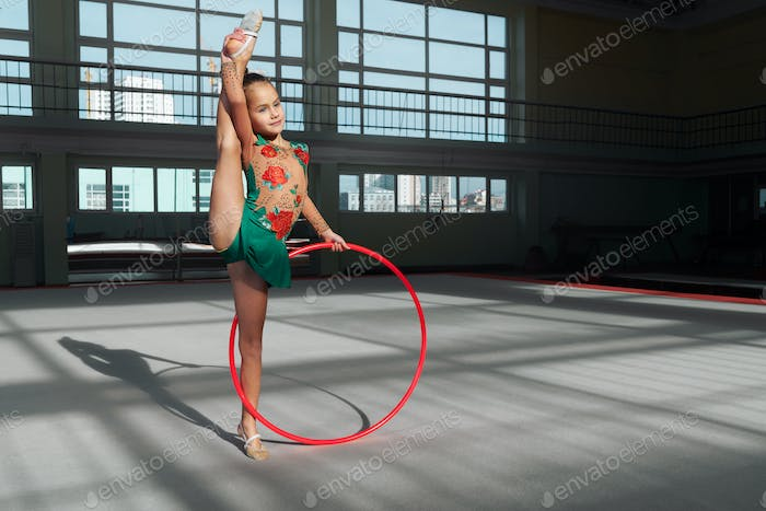 Little girl doing exercise with hoop