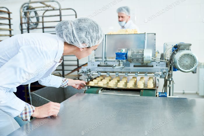 Factory worker pulling tray with pastry from confectionery machine